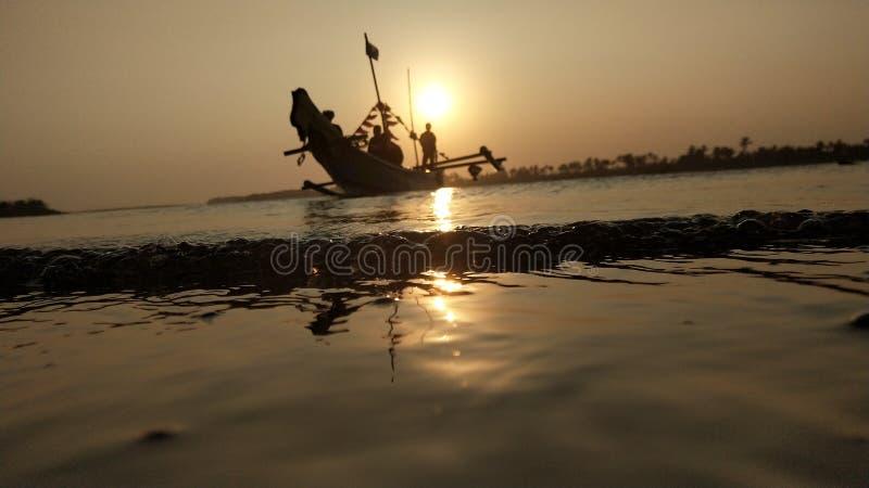 crepúsculo quando o sol se ajustar na borda de uma lagoa romântica da praia ao olhar a sombra do barco imagem de stock royalty free
