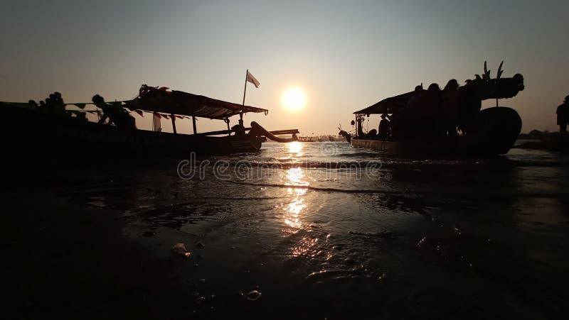crepúsculo quando o sol se ajustar na borda de uma lagoa romântica da praia ao olhar a sombra do barco imagem de stock