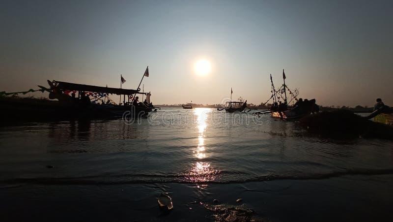 crepúsculo quando o sol se ajustar na borda de uma lagoa romântica da praia ao olhar a sombra do barco imagens de stock