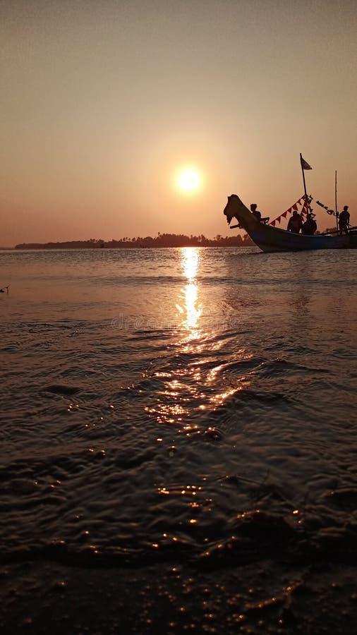 crepúsculo quando o sol se ajustar na borda de uma lagoa romântica da praia ao olhar a sombra do barco fotografia de stock royalty free