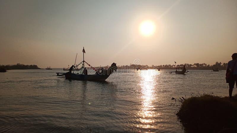 crepúsculo quando o sol se ajustar na borda de uma lagoa romântica da praia ao olhar a sombra do barco fotos de stock