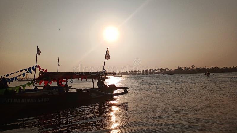 crepúsculo quando o sol se ajustar na borda de uma lagoa romântica da praia ao olhar a sombra do barco fotos de stock royalty free