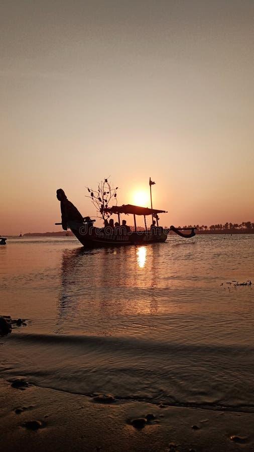 crepúsculo quando o sol se ajustar na borda de uma lagoa romântica da praia ao olhar a sombra do barco foto de stock