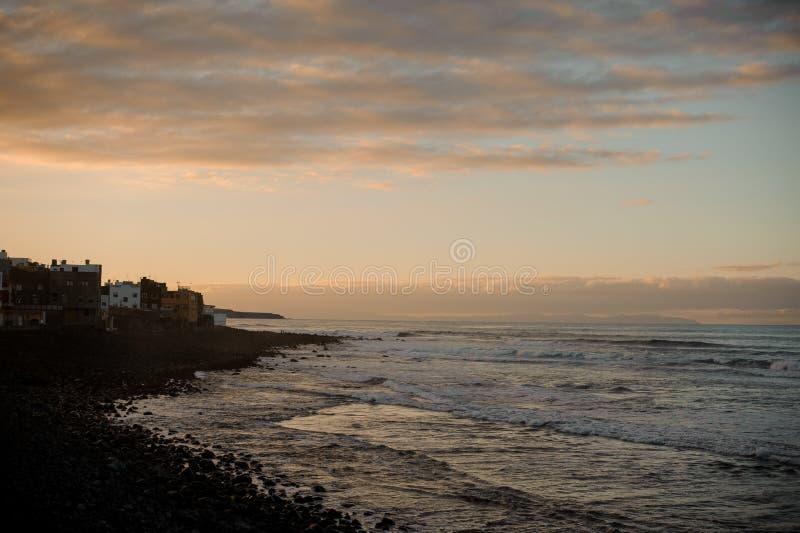 Crepúsculo sobre costa de la ciudad antigua y de mar con las ondas debajo del cielo fotografía de archivo