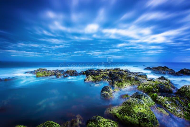 Crepúsculo sobre o mar azul calmo sobre o oceano e o céu nebuloso imagens de stock