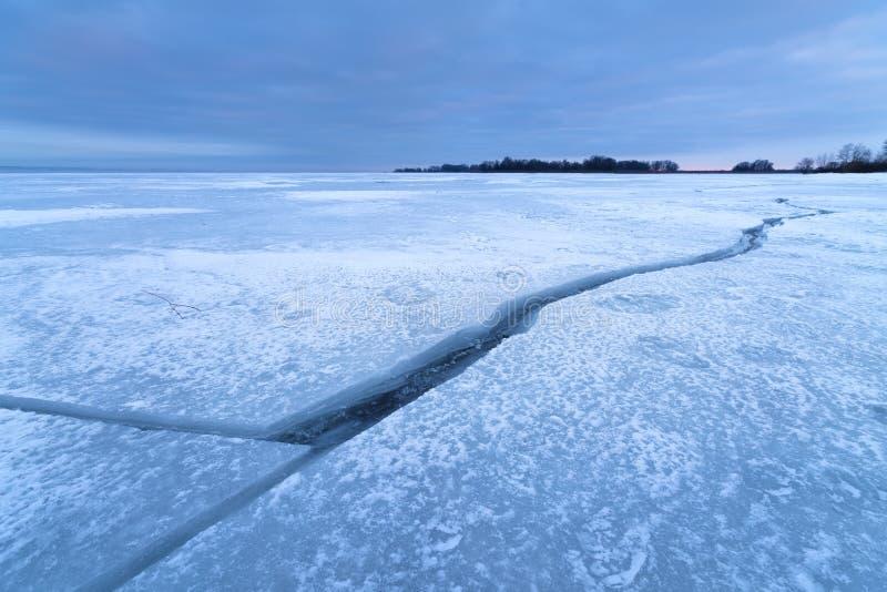 Crepa nel ghiaccio un tramonto nuvoloso fotografie stock libere da diritti