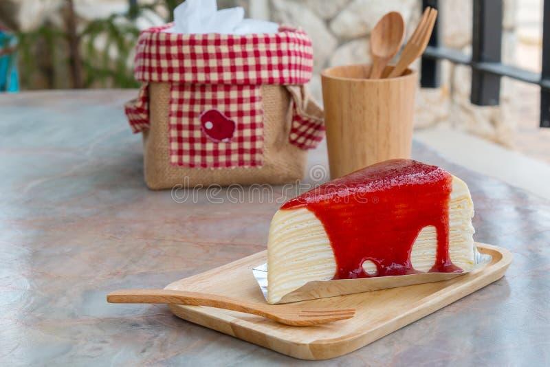 Crepe το κέικ με τη σάλτσα φραουλών στον ξύλινο δίσκο στοκ εικόνα