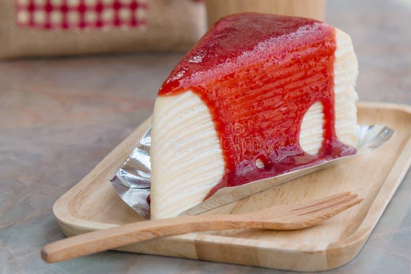 Crepe το κέικ με τη σάλτσα φραουλών στον ξύλινο δίσκο στοκ εικόνες