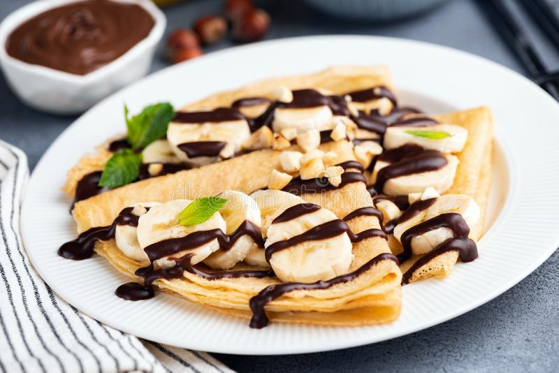 Crepe with banana and chocolate. Sauce on white plate, closeup view, selective focus. Tasty dessert royalty free stock photos