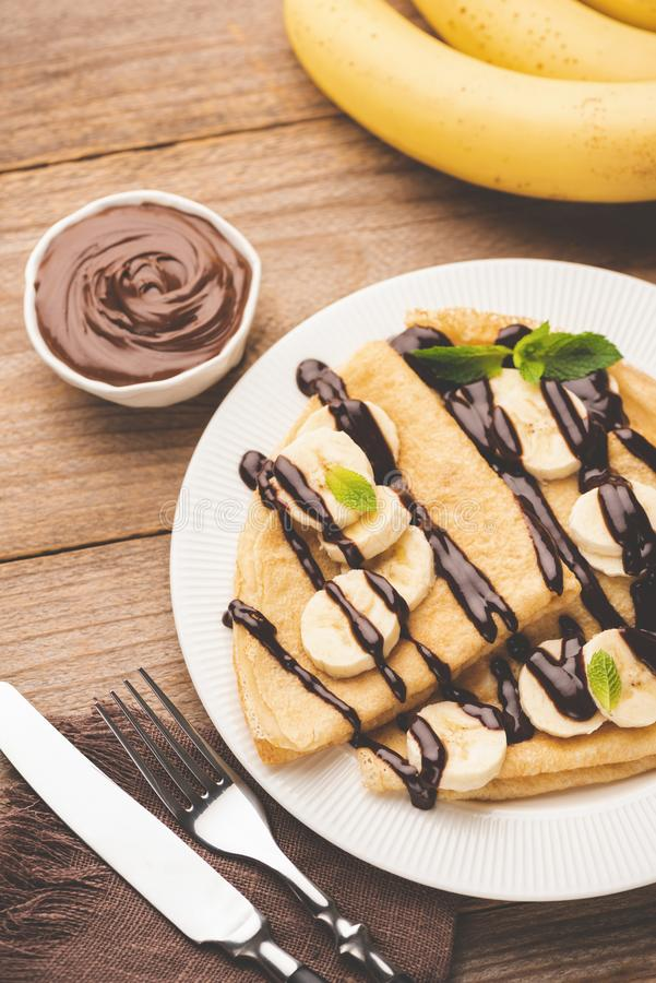 Crepe with bananas and chocolate on white plate. On wooden table served with chocolate hazelnut spread, top view royalty free stock photography