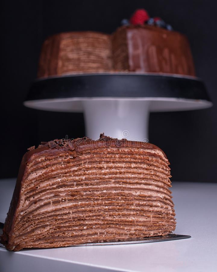 Crepe Cake. Chocolate crepe cake with berries. Slice of delicious chocolate crepe cake. A Lot of layers . The whole cake stay on a cake stand on back background royalty free stock images