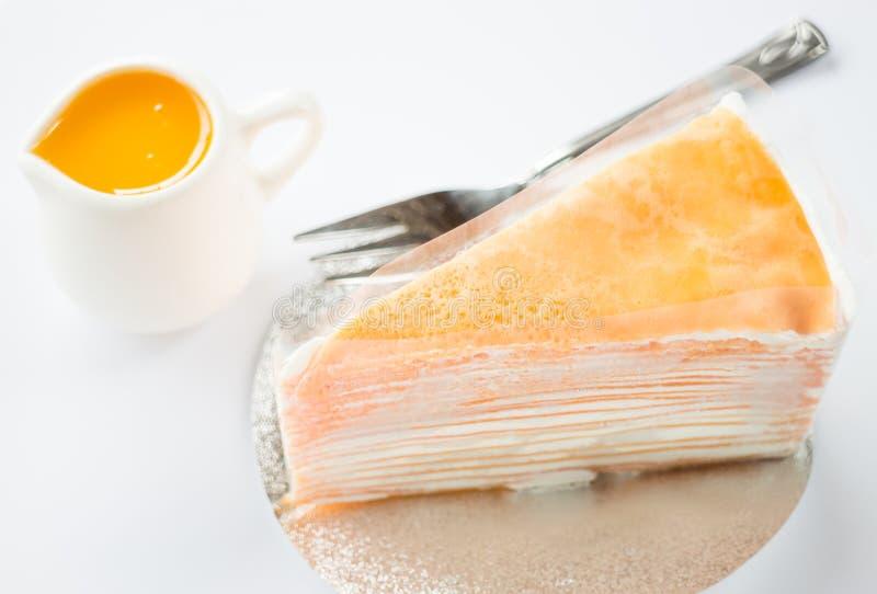 Crepe cake with orange sauce on white background. Stock photo royalty free stock image