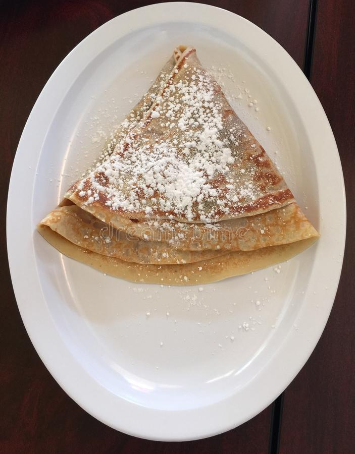 A Crepe Covered in Powdered Sugar. A delicious chocolate crepe sprinkled with powdered stock image