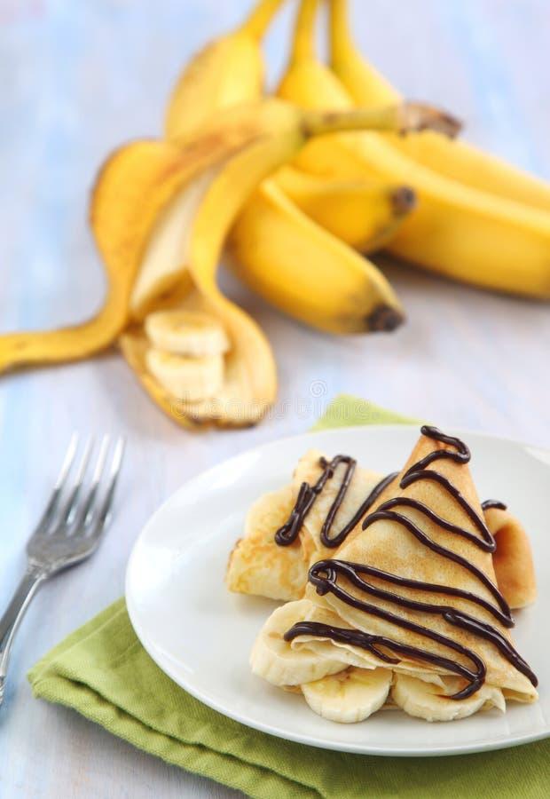 Crepe della banana con lo sciroppo di cioccolato fotografia stock