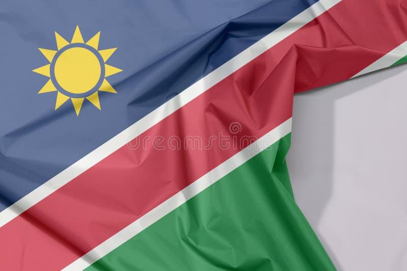 Crepe e vinco da bandeira da tela de Namíbia com espaço branco imagem de stock