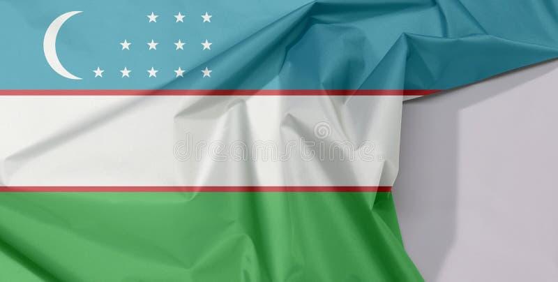 Crepe e vinco da bandeira da tela de Usbequistão com espaço branco fotos de stock