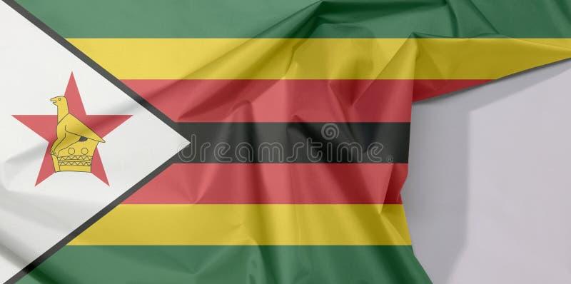 Crepe e vinco da bandeira da tela de Zimbabwe com espaço branco fotografia de stock royalty free