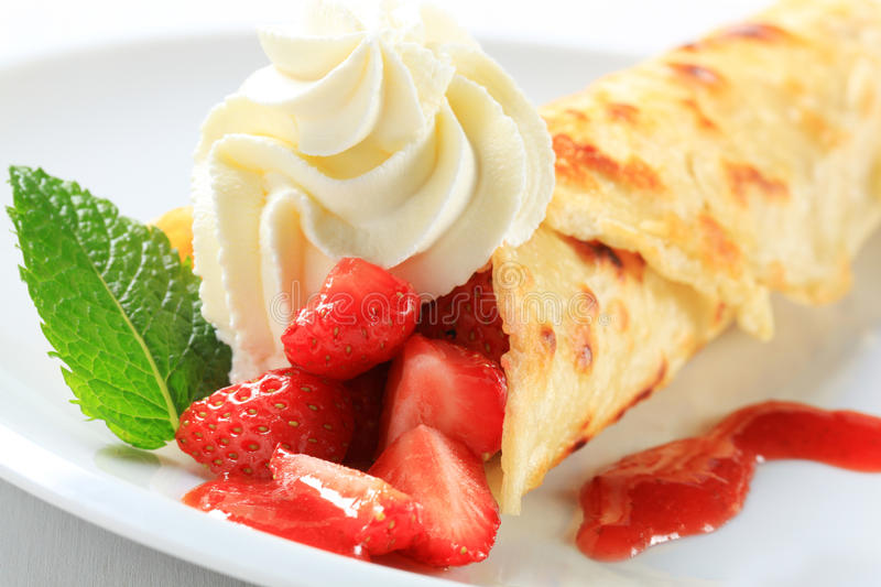 Crepe with fresh strawberries. And whipping cream stock image