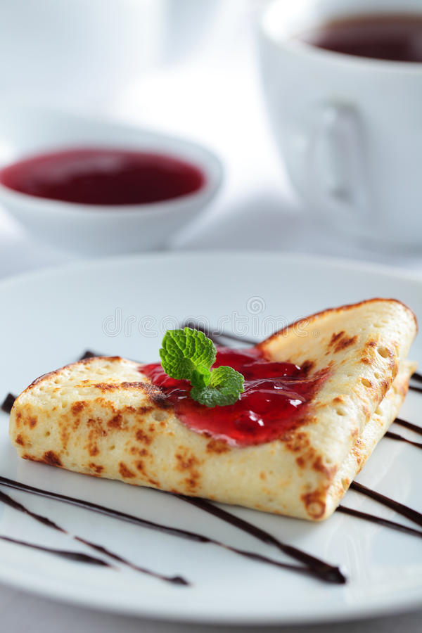 Crepe with jam. Crepe with red currant jam and mint stock photo