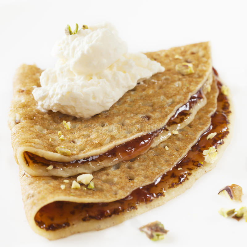 Crepe with Jam and Cream. Commercially produced crepe with strawberry jam and whipped cream, topped with pistachios stock photography