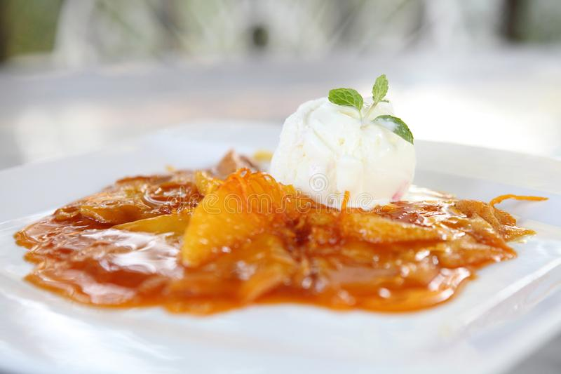 Crepe with orange sauce and ice cream. On a plate royalty free stock image