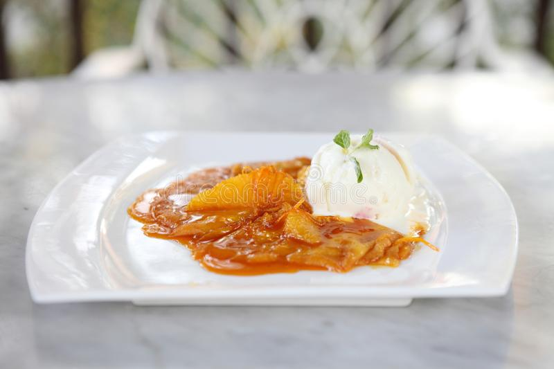Crepe with orange sauce and ice cream. On a plate stock photo