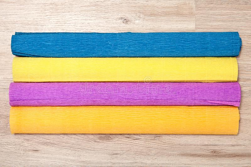 Four multicolored rolls of corrugated paper lie on board. stock photos