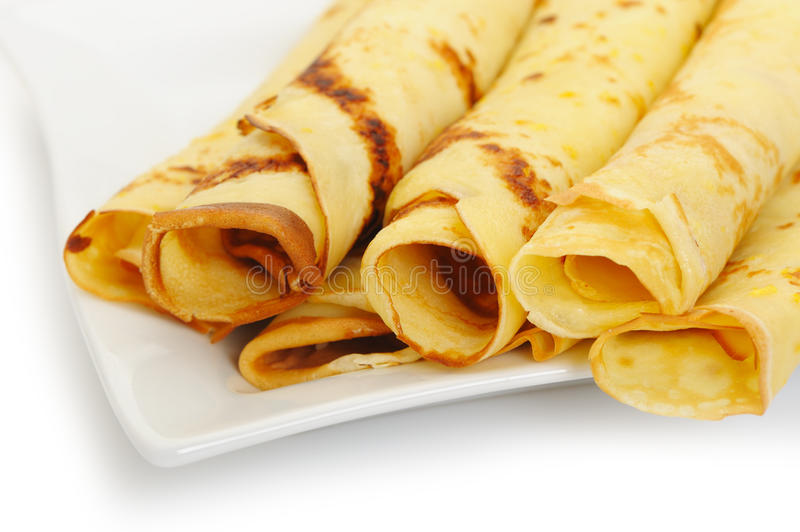 Crepe roll up a tubule on a plate. It is isolated on a white background royalty free stock image