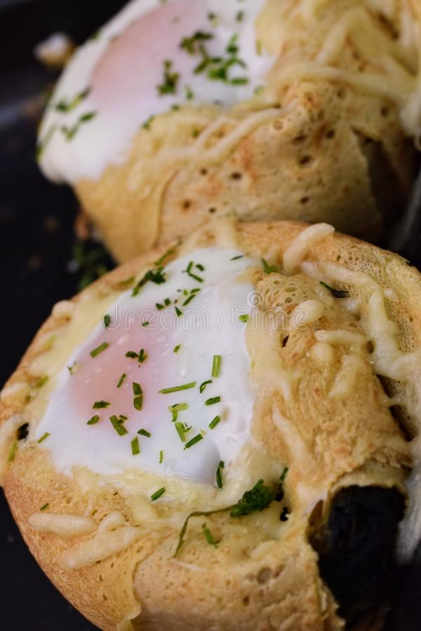 Crepe rolls. Stuffed with spinach, mushrooms, goat cheese and topped with an egg...home made tasty food egghome royalty free stock images
