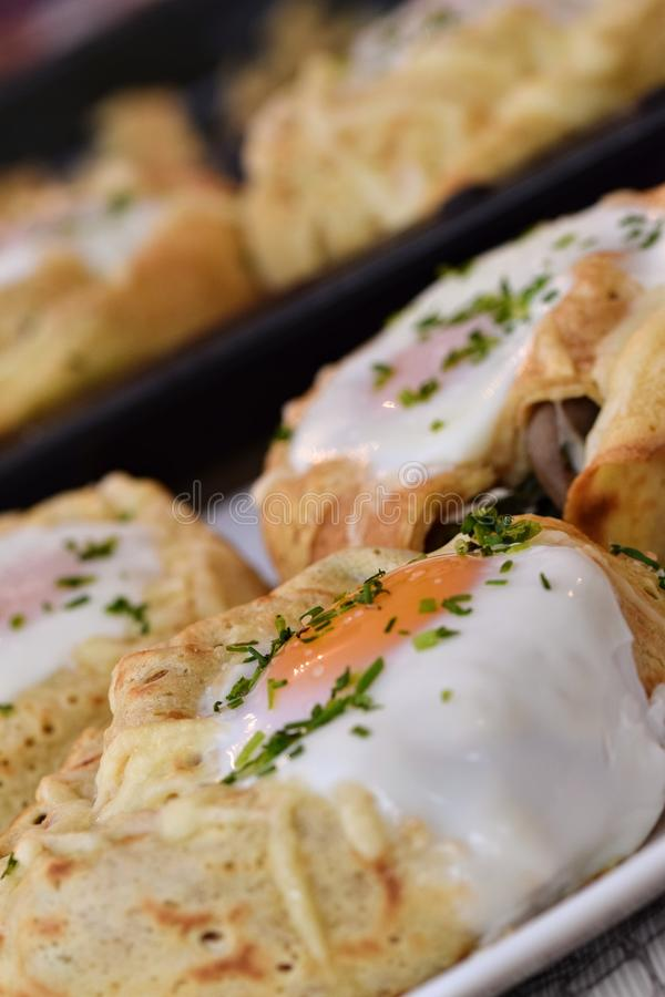 Crepe rolls. Stuffed with spinach, mushrooms, goat cheese and topped with an egg...home made tasty food egghome royalty free stock photos