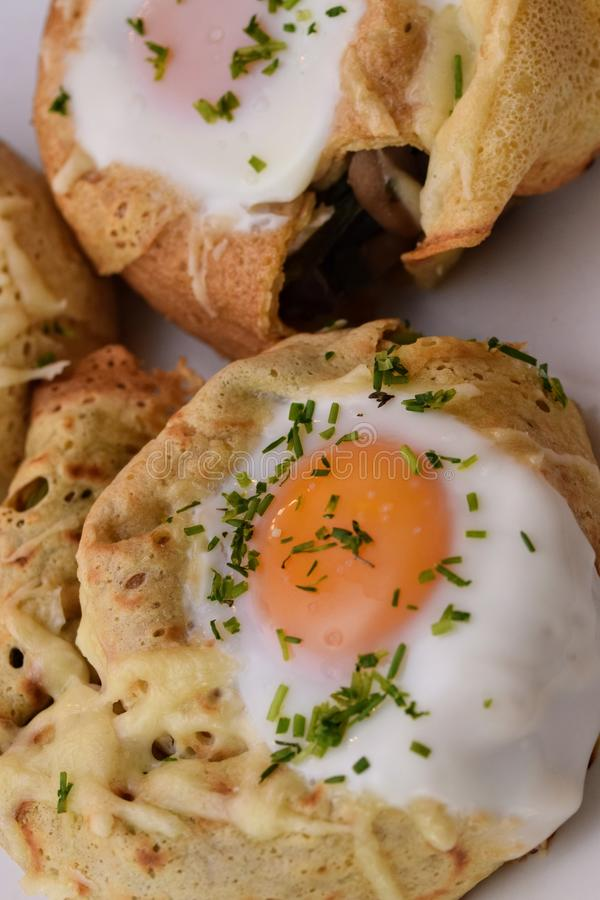 Crepe rolls. Stuffed with spinach, mushrooms, goat cheese and topped with an egg...home made tasty food egghome royalty free stock photography