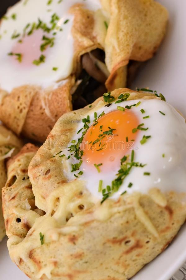 Crepe rolls. Stuffed with spinach, mushrooms, goat cheese and topped with an egg...home made tasty food egghome royalty free stock image
