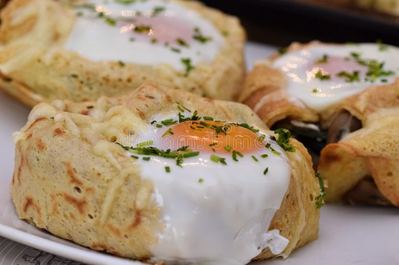 Crepe rolls. Stuffed with spinach, mushrooms, goat cheese and topped with an egg...home made tasty food egghome royalty free stock photo