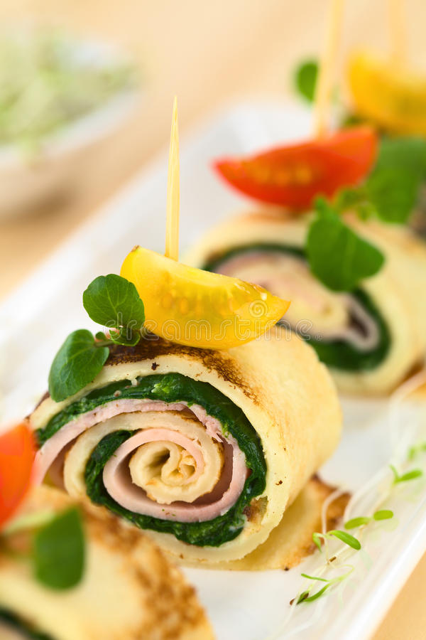 Crepe Rolls Filled with Ham and Spinach. Crepe rolls as finger food filled with spinach and ham garnished with cherry tomato and watercress (Selective Focus stock image