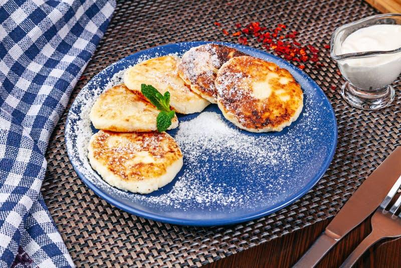 Crepe ucraniana hecha en casa tradicional del queso con crema agria en la placa azul imágenes de archivo libres de regalías