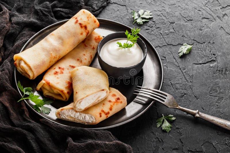 Crepes με το τυρί εξοχικών σπιτιών, τα πράσινα και την ξινή κρέμα στο μαύρο πιάτο πέρα από το σκοτεινό υπόβαθρο Εβδομάδα ή Shrove στοκ εικόνες με δικαίωμα ελεύθερης χρήσης