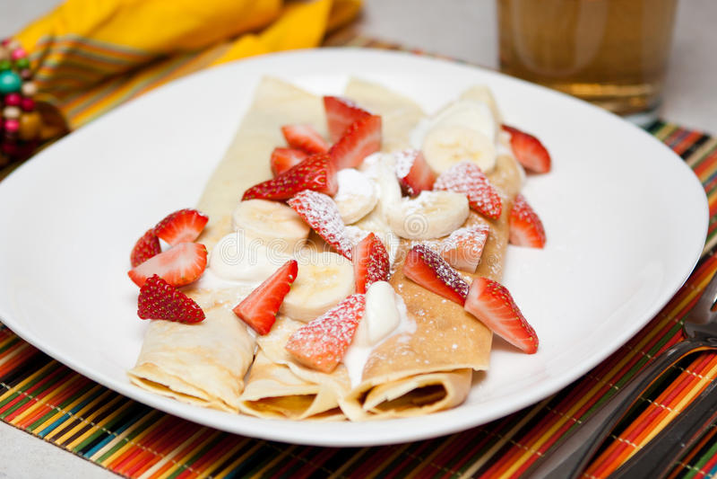 Crepes με τη φράουλα, μπανάνα και κτυπά την κρέμα στοκ εικόνες