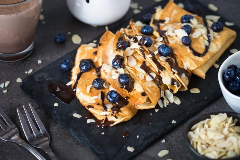 Crepes με τις νιφάδες αμυγδάλων βακκινίων και τη σάλτσα σοκολάτας στο bla στοκ εικόνες με δικαίωμα ελεύθερης χρήσης