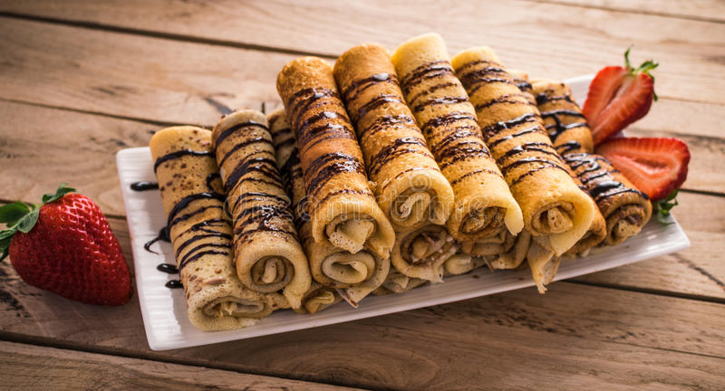 Crepes с nutella и клубниками деревянное предпосылки деревенское стоковые изображения