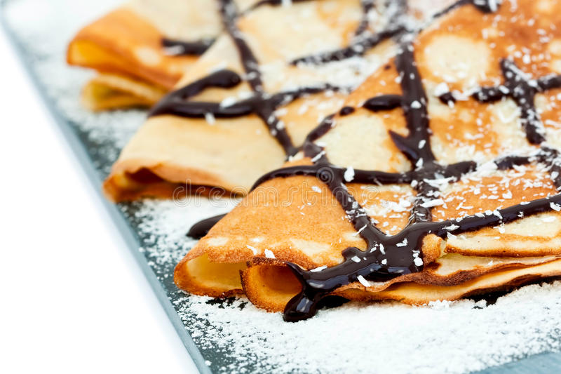 Crepes. With chocolate syrup drizzle and coconut shavings royalty free stock photos