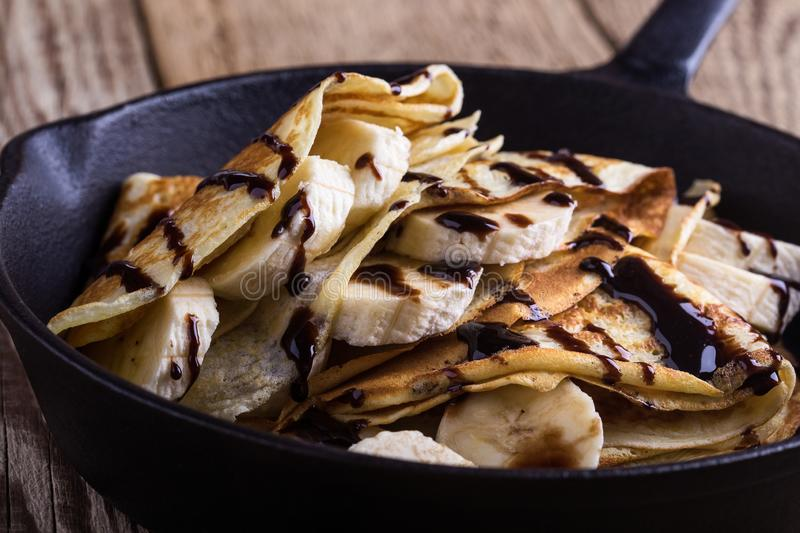 Crepes with bananas and chocolate topping for breakfast royalty free stock image
