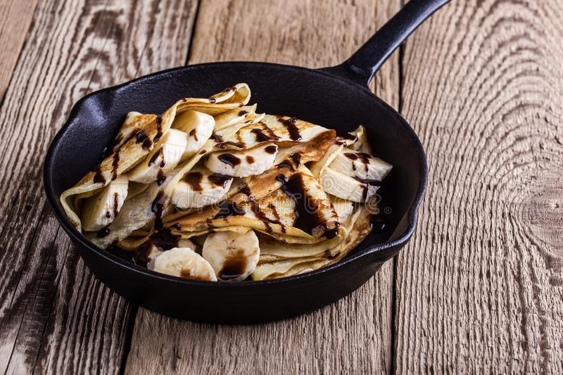 Crepes with bananas and chocolate topping for breakfast royalty free stock images