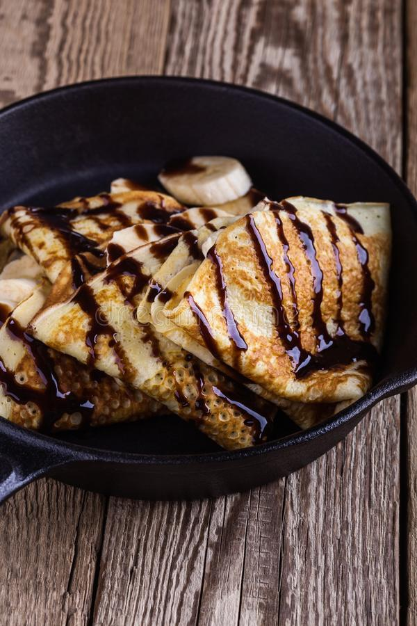 Crepes with bananas and chocolate topping for breakfast stock photos