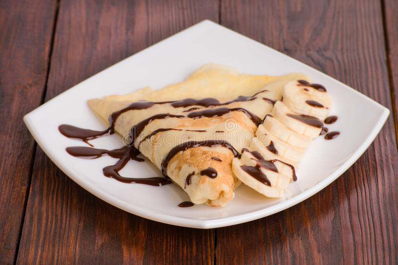 Crepes with bananas and cream. On white background royalty free stock photos