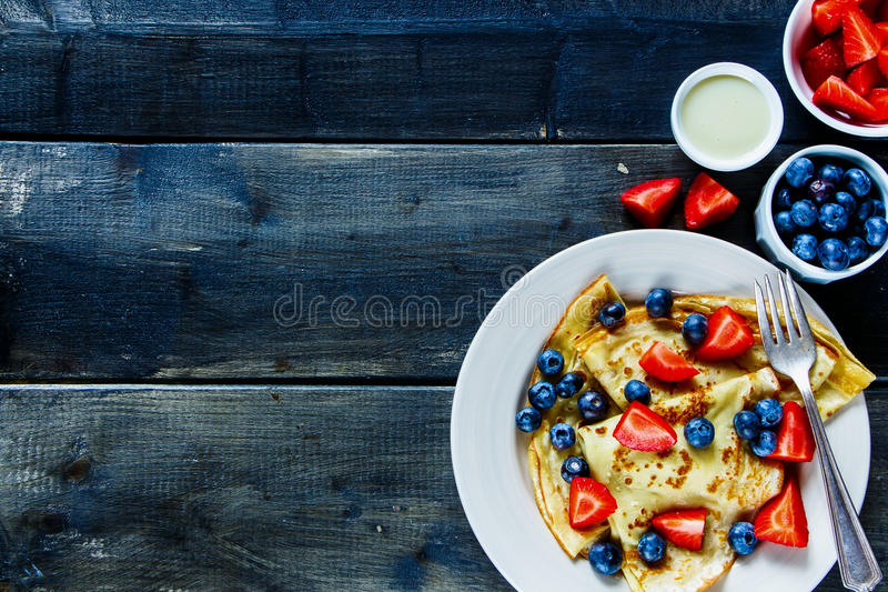 Crepes with berries. Delicious homemade thin pancakes or crepes with fresh berries and cream on plate over rustic wooden background, top view, free text space stock photo