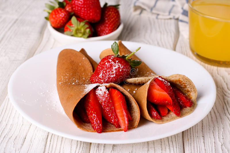 Crepes with berries and orange juice, horizontal, closeup. Crepes with berries and orange juice, horizontal stock photo