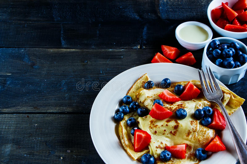 Crepes with berries. Tasty homemade thin pancakes or crepes with fresh berries and cream on plate over rustic wooden background, selective focus, free text royalty free stock image