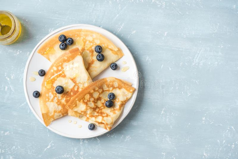 Crepes with blueberries and honey. Homemade pancakes, crepes on blue table, copy space royalty free stock photography
