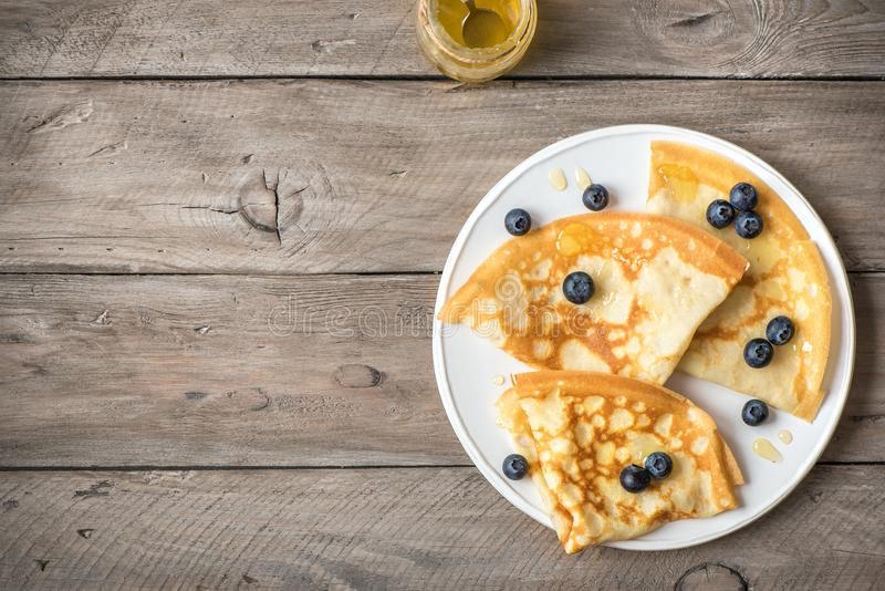 Crepes with blueberries and honey. Homemade pancakes, crepes on wooden table, copy space royalty free stock photo