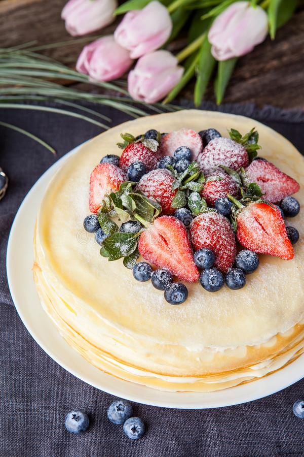 Crepes cake with cottage cheese and strawberry, selective focus. Homemade crepes cake with strawberry on rustic background. Cooking fresh homemade breakfast stock images